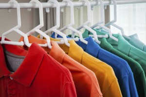 Line of hanging polo shirts in a closet.