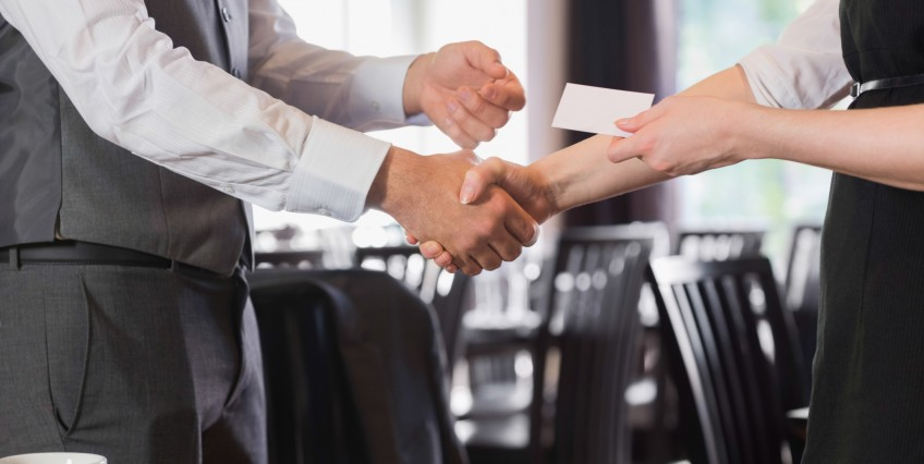 A man and a woman shaking hands and exchanging a business card.