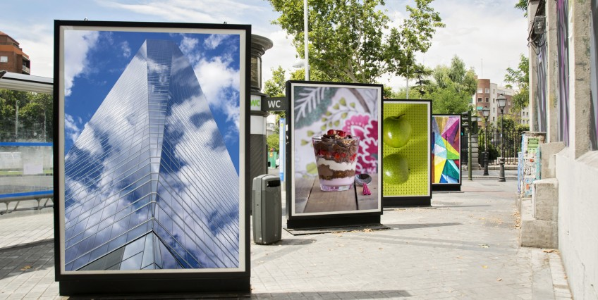 A line of billboards stands on the sidewalk outside on a summer's day.