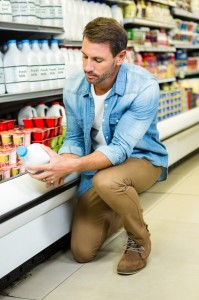 A handsome man looks at a carton of milk.