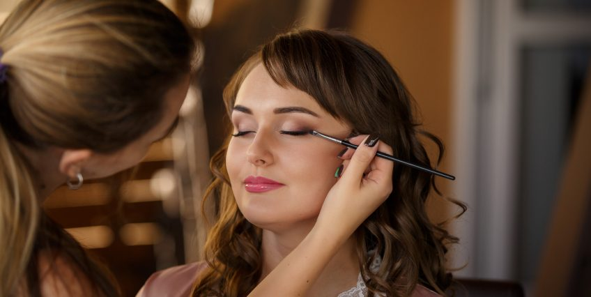 Beautician working on model's eye makeup